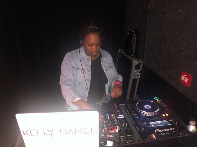 DJ Kelly Daniel from London performs behind the decks.